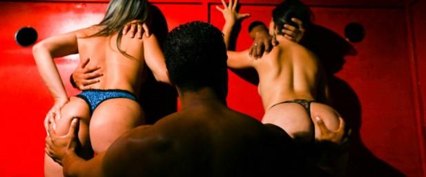 Um homem com duas mulheres em uma festa suingue